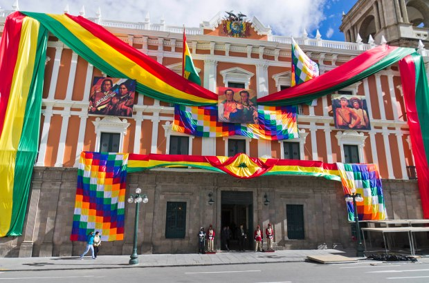 the legislative palace draped with the rainbow colored Aymara flag, the Bolivian flag & the flag of La Paz