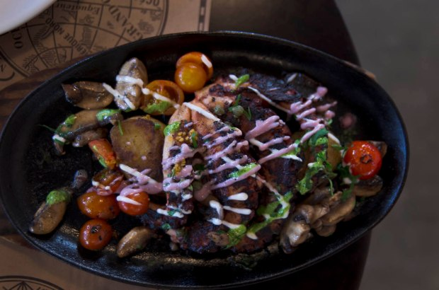 pulpo a la parrilla served on a sizzling platter